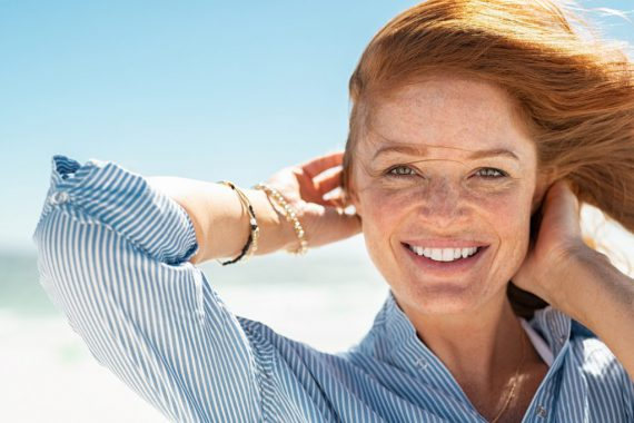 Woman smiling in the wind by the beach