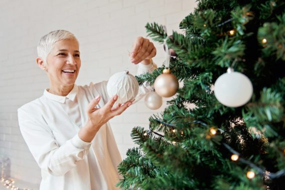 Beautiful woman decorating a Christmas tree