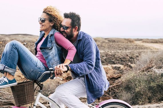 happy adult caucasian, couple having fun with bicycle in outdoor leisure activity. concept of active playful people with bike during vacation - everyday joy lifestyle without age limitation - man carry woman and both have fun and laugh a lot with wind in