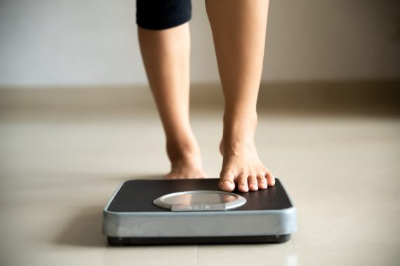 female_legs_stepping_on_scale
